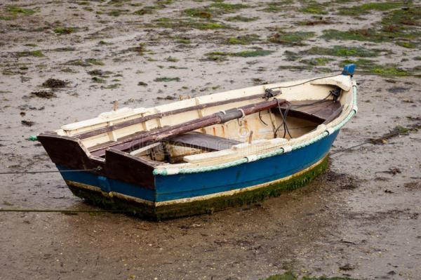 little-fishing-boat-stranded-wet-sand-low-tide-90786222